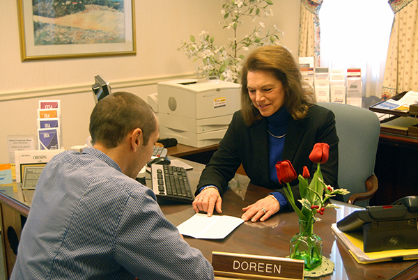 Picture of a woman, sitting behind a desk explaining paperwork to a man.